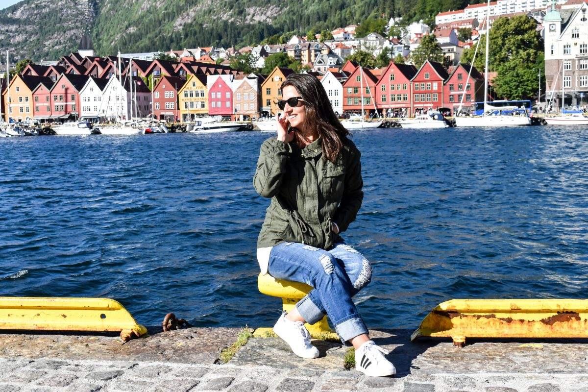 Erin sits along Bergen's harbor in front of a row of colorful buildings