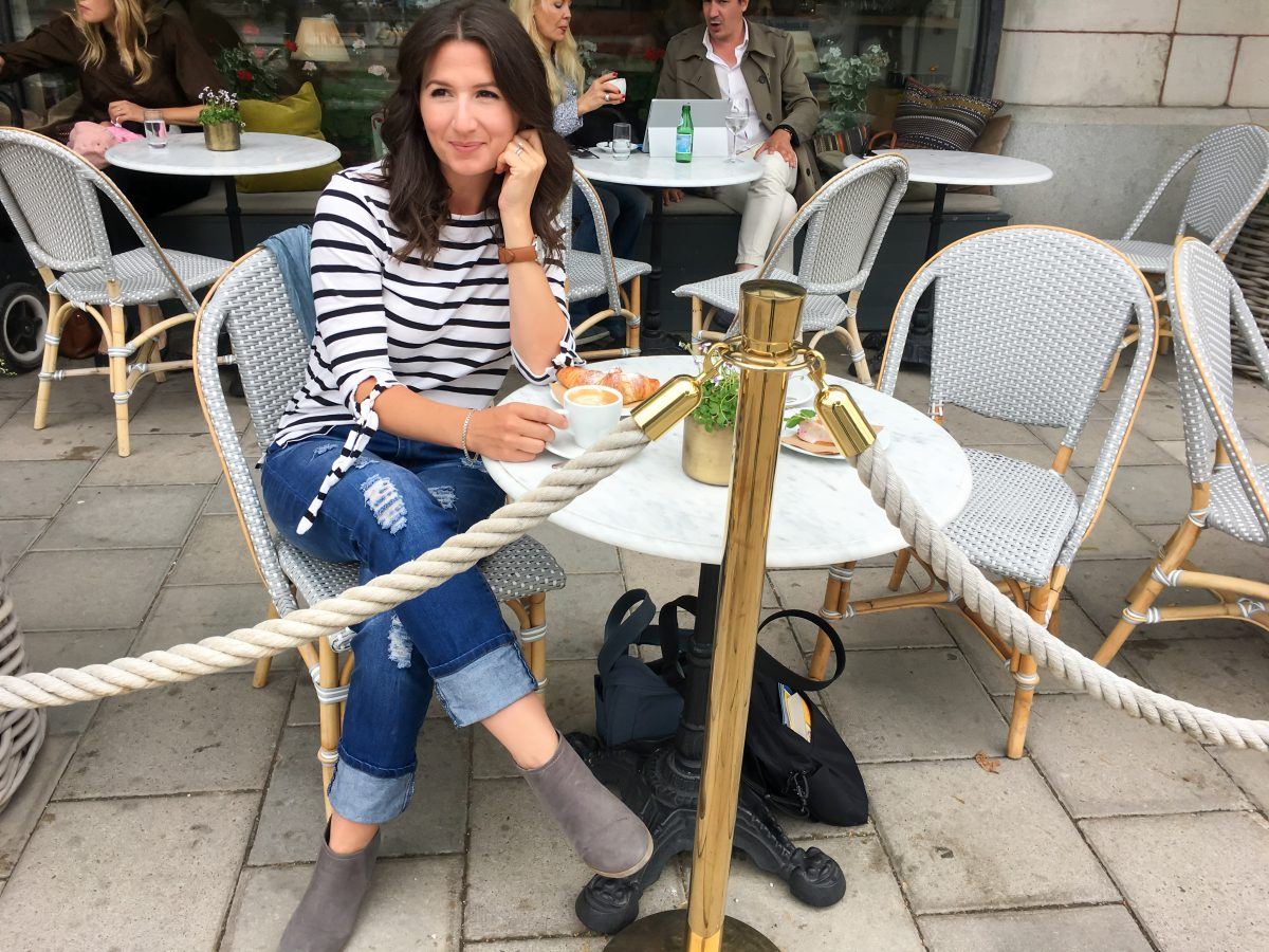 Erin sips a cappuccino at a cafe in Stockholm wearing a nautical striped top.