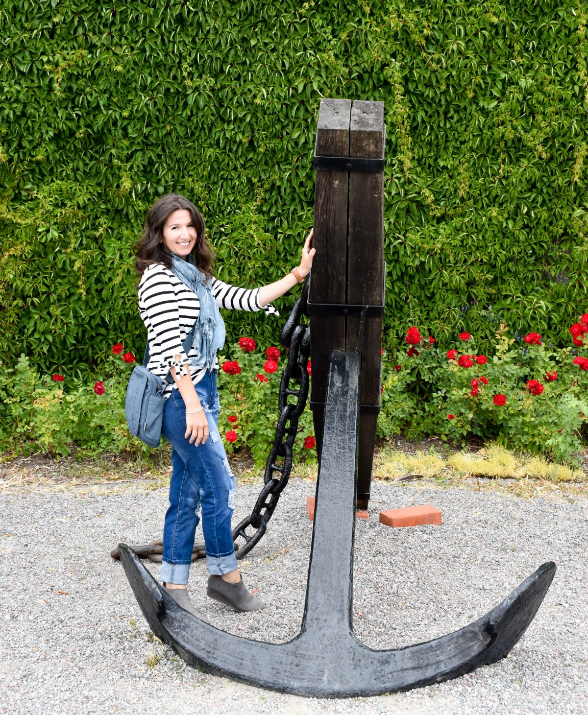 Erin poses with a large vintage anchor in Vaxholm, Sweden wearing a nautical striped tee.