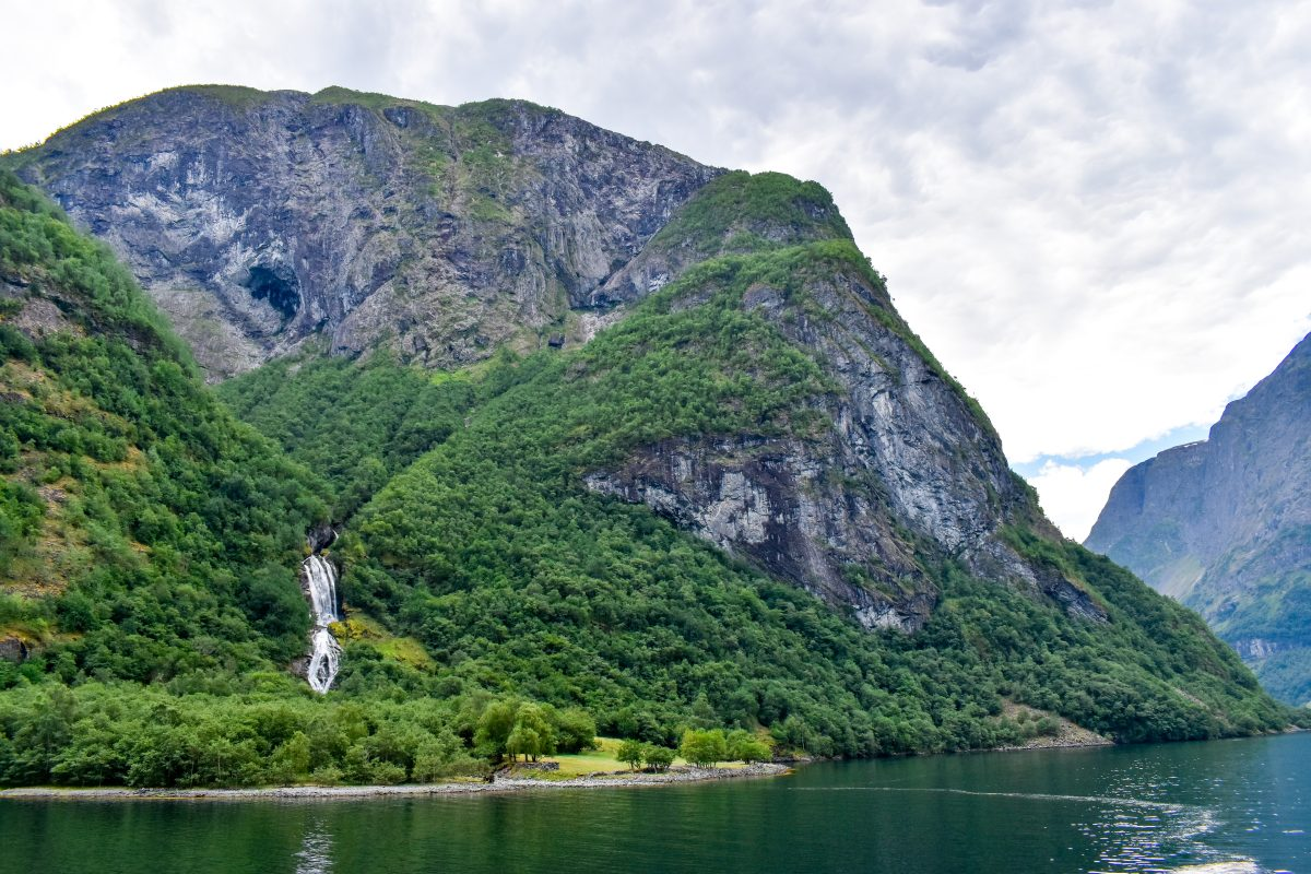 A waterfall cascades down a fjord in Norway