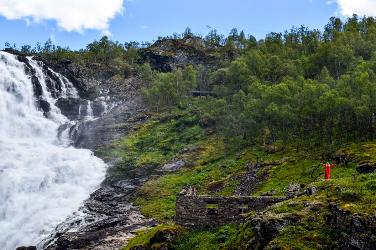 A dancing Huldra appears next to a waterfall on the Norway in a Nutshell tour