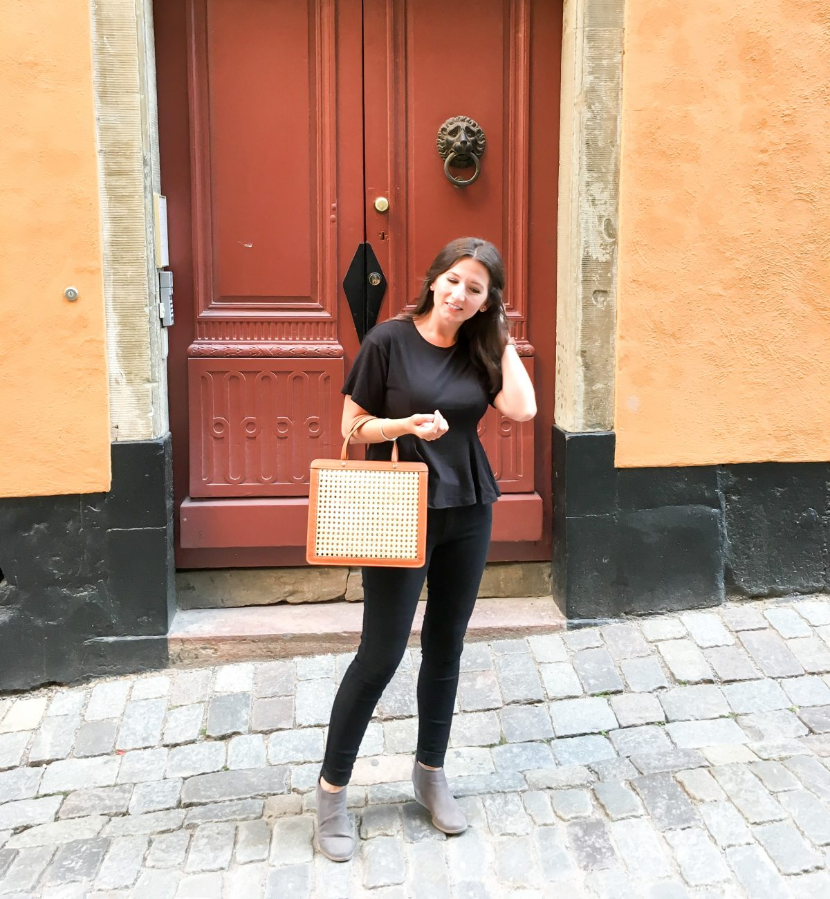 Erin wears a monochromatic look with a Palmgrens rattan collection bag to dinner in Stockholm, Sweden.