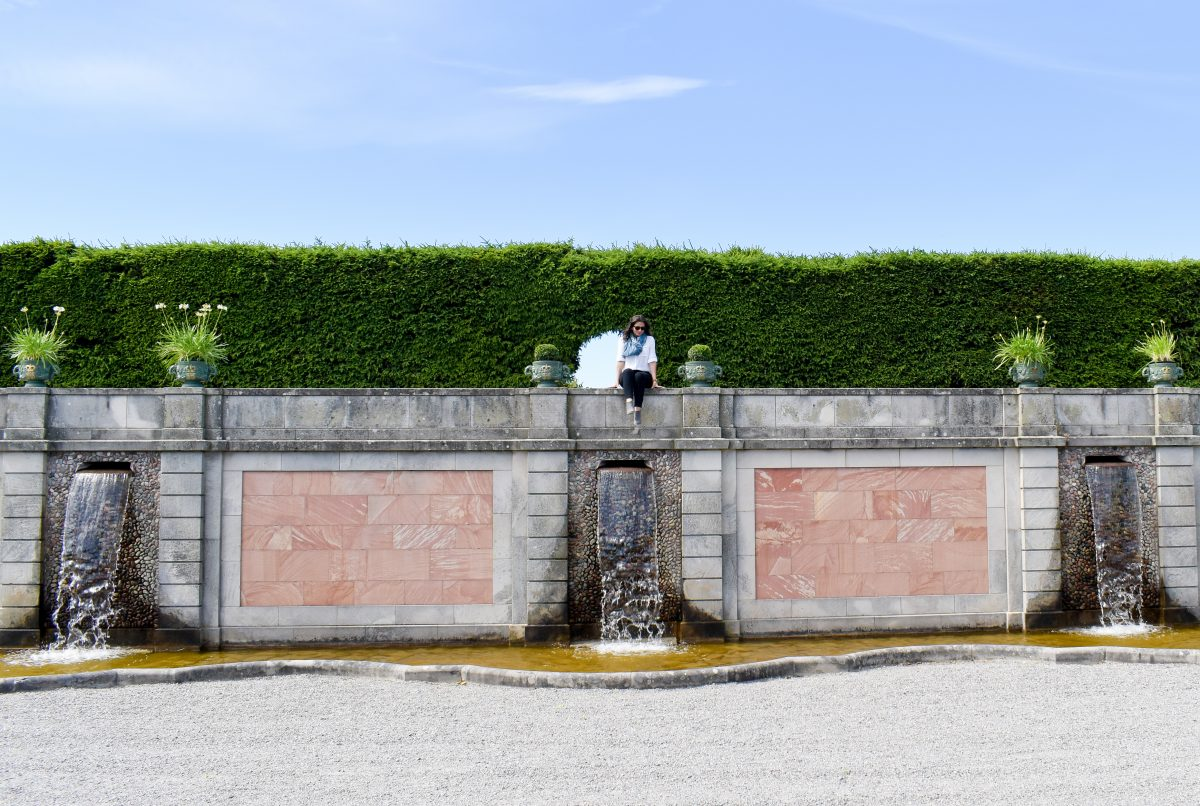 Erin sits atop a stone fountain in the Drottningholm Palace gardens in Sweden