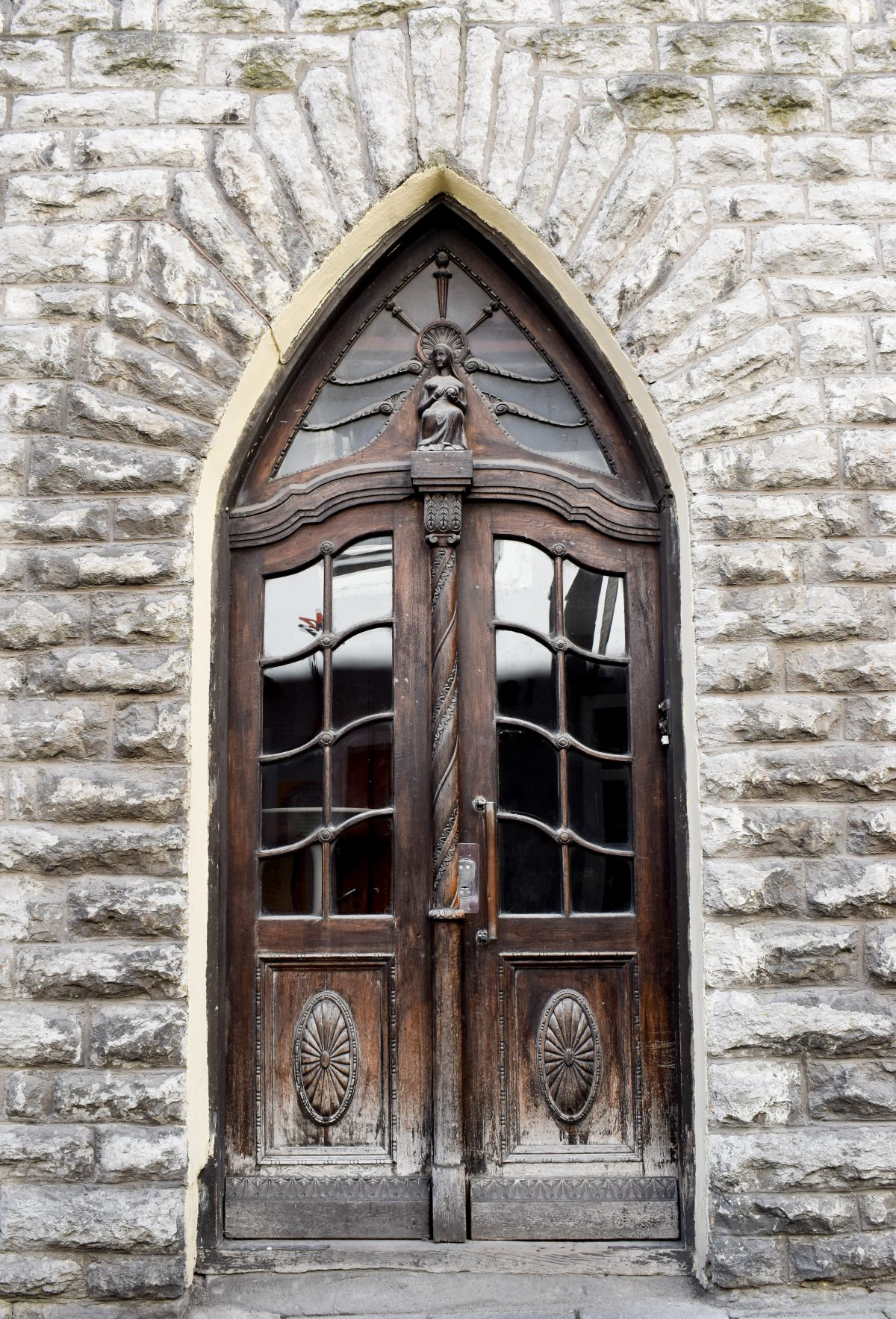 Old carved wooden door surrounded by stone in Tallinn Estonia