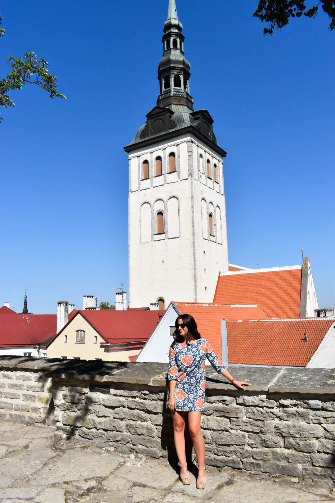 Erin leans against a stone wall in front of a tower in Tallinn Estonia