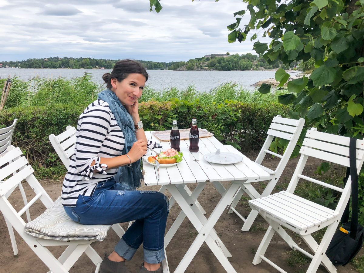 Erin enjoys a seaside lunch in Vaxholm, Sweden wearing a nautical striped tee.