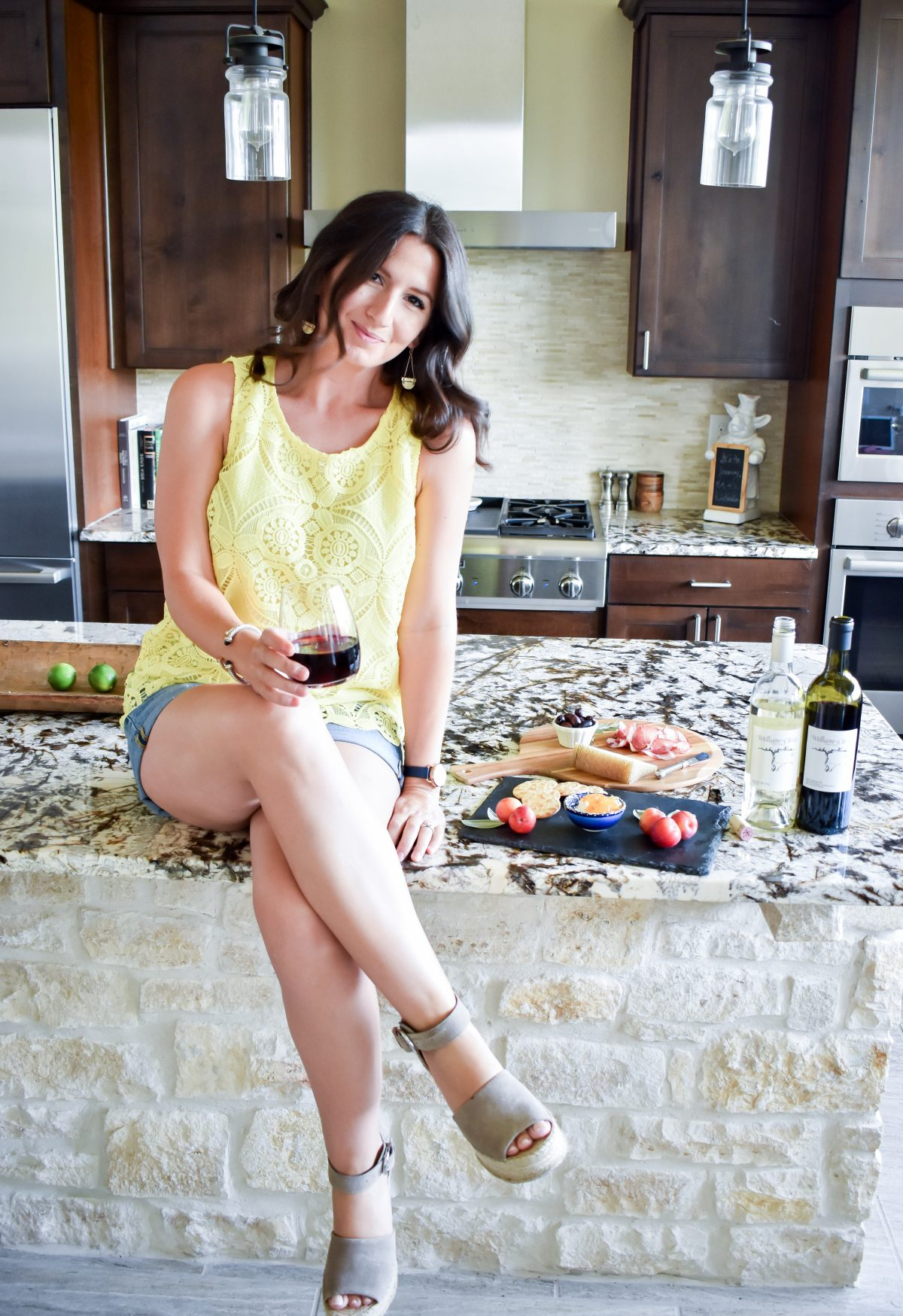 Erin sits on her kitchen island ready to entertain with simple summer wine and cheese boards.