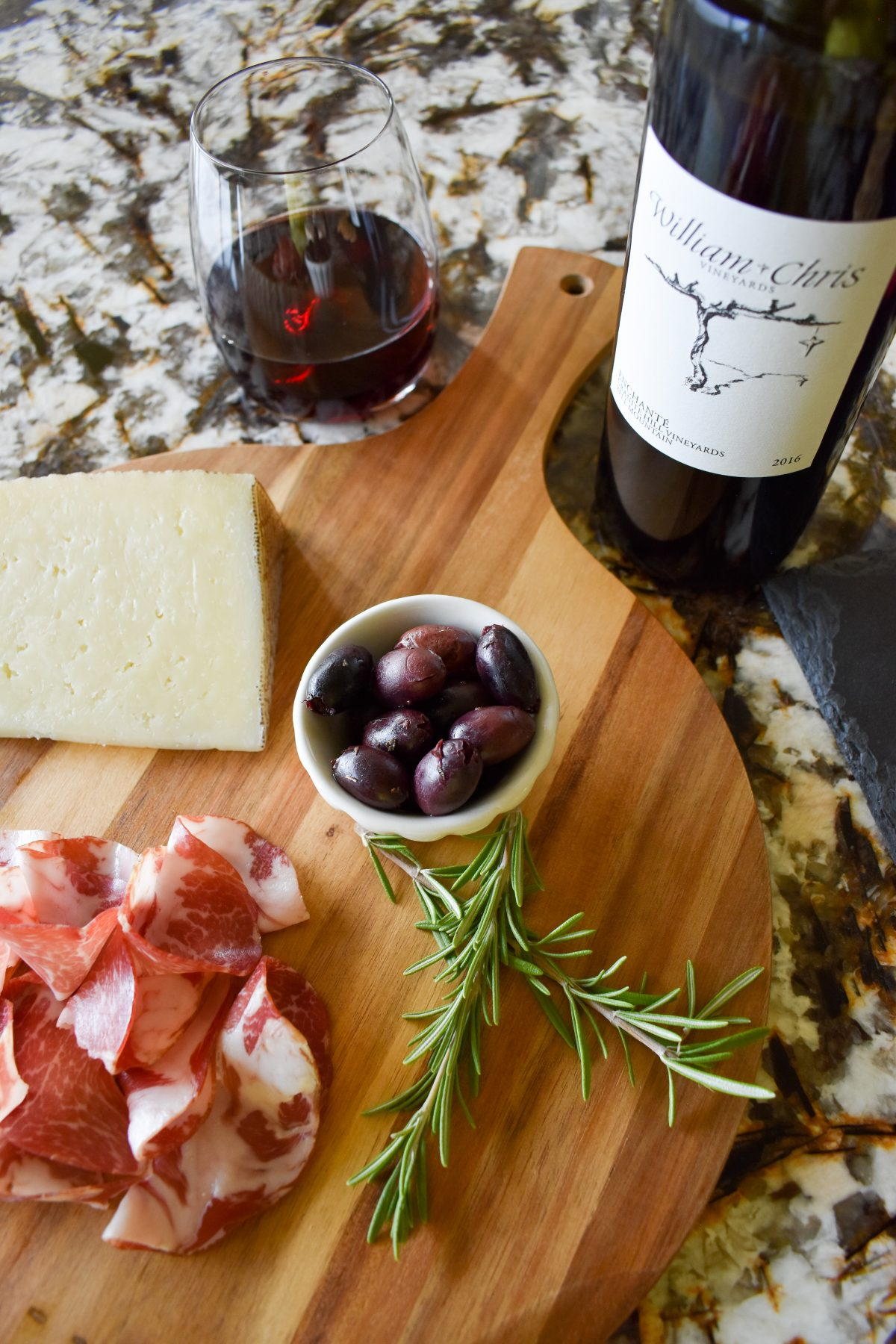 Enchanté red wine from William Chris Vineyards with a charcuterie board of coppa, olives, and manchego cheese.