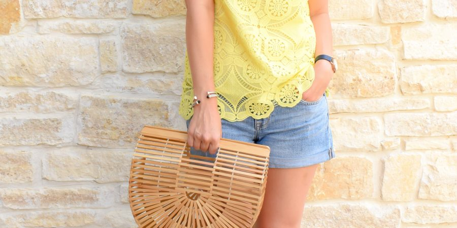 Erin wears a yellow lace top, denim cutoffs, and carries a cult gaia bamboo bag