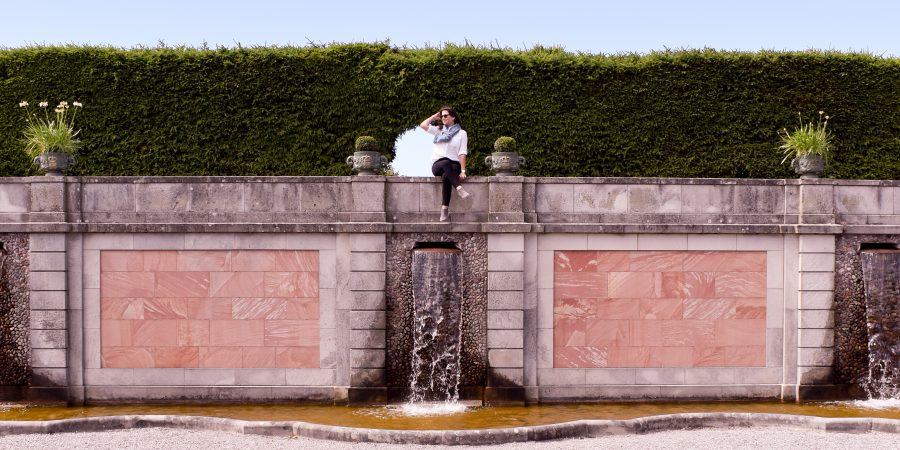Erin sits on the fountain wall in the gardens of Drottningholm Palace