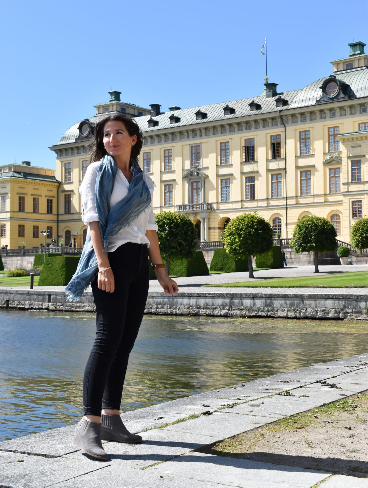 Erin stands in front of Drottningholm Palace along the water's edge